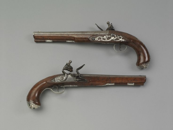 This Pair Of Silver Mounted Carved Flintlock Pistols From