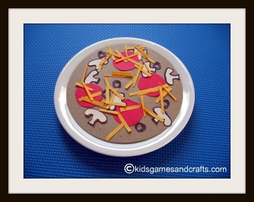 Paper pizza made with circle of cardboard, and construction paper goodies for toppings: red circles for pepperoni, white mushroom shapes, yellow rectangles for cheese, green squares for peppers.