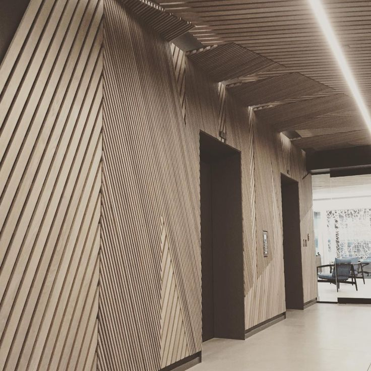 Elevator lobby: thin wooden slats placed at opposing angles spell 'NIKE' on wall and ceiling