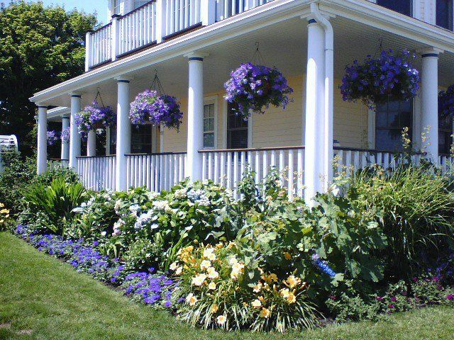 Beautiful hanging basketslove the purple outdoors for Front porch flower bed ideas