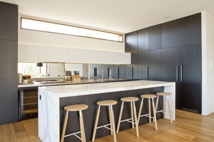Cucina con mobili neri, isola con piano in marmo bianco e paraschizzi a specchio