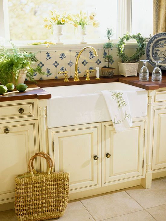 A white cast-iron farmhouse sink is framed by decorative pilasters, a feature of the cabinetry. White-and-blue tile backsplash and a wooden countertop enhance the country feel of the kitchen. And nothing brightens up a work area like placement in front of a window.