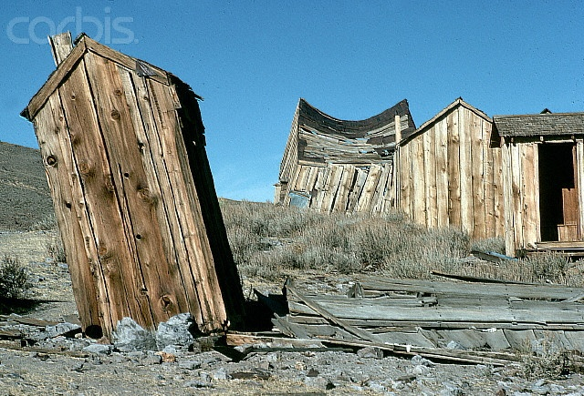 A leaning outhouse and sagging building in the ghost town of Bodie State Historical Park. California.