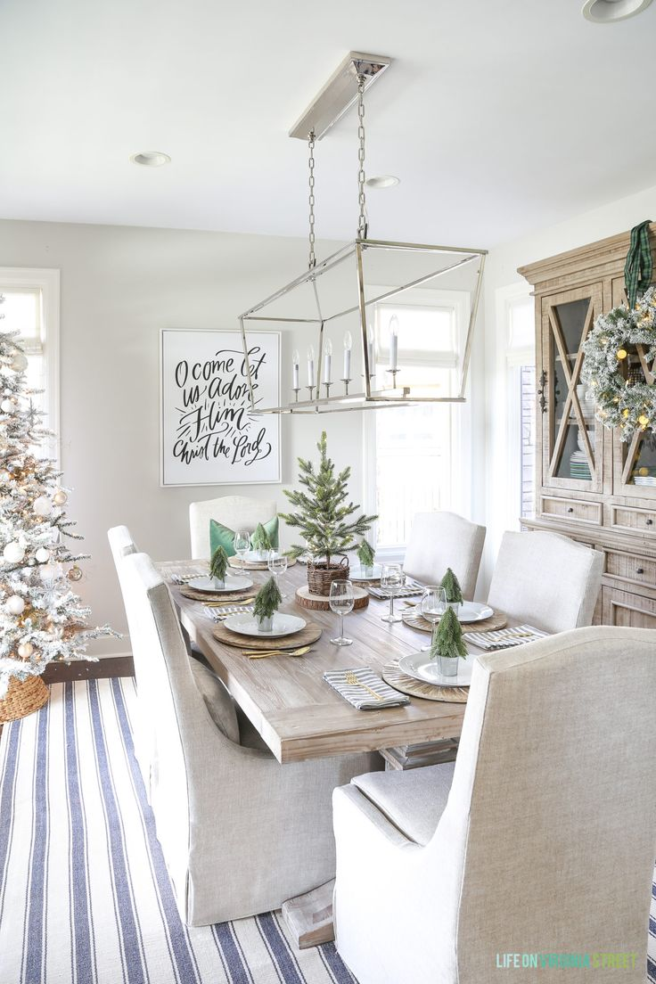 Coastal dining room with blue and white striped rug, linen chairs, reclaimed wood dining table, Darlana linear pendant and a flocked Christmas tree. #christmaslivingroom #christmasdecor #livingroom #whitedecor