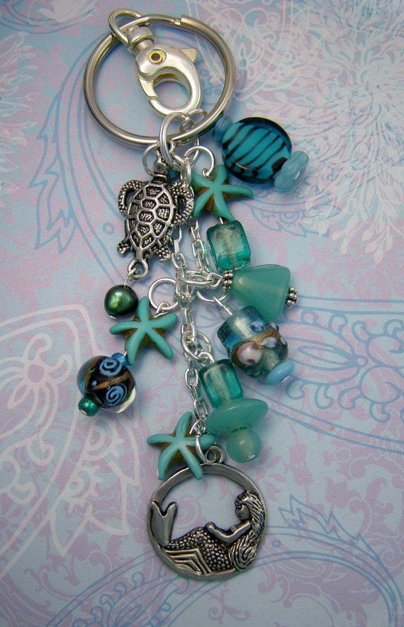 """Sea Foam green colors accent multishaped glass beads, starfish beads, lampwork glass, a swimming sea turtle and dreaming mermaid charms. This clip on dangles about 6"""" long- which includes the lobster clip. Comes with a large clasp 1 1/8"""", to clip onto purses, belts, beach bags, jeans, tote bags, car mirror, wherever you need a splash of the ocean! Lovely beachy gift."""
