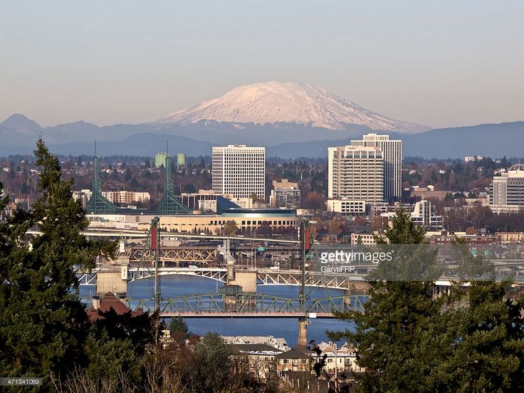 A view looking down to the Willamette River with trees, bridges, Convention Center, Skyscrapers and Mt St Helens (Washington State) in the background. This is downtown Portland, Oregon area.