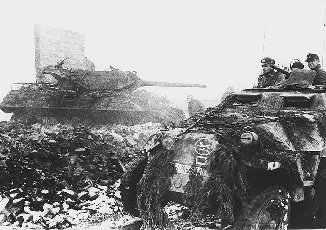 German soldiers of 116. Panzer-Division 'Windhund' in a Sd.Kfz. 251/3 Ausf.D passing by a destroyed M10 Tank Destroyer during the Battle of Hürtgen Forest, in the town of Schmidt, North Rhine-Westphalia, Germany. 9 November 1944.