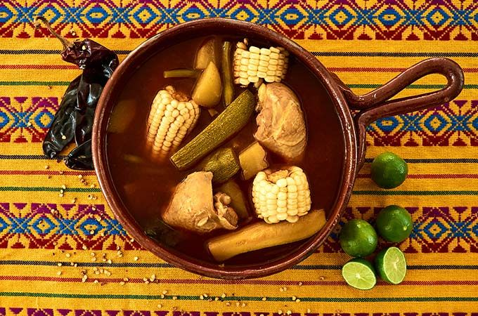 Clemole Rojo de Pollo - RED CHILE MEXICAN CHICKEN STEW / SOUP - Soup or stew? You call it. Whole chicken legs and thighs cooked with large chunks of corn, chayote, zucchini squash and green beans in a red guajillo chile and tomato broth.