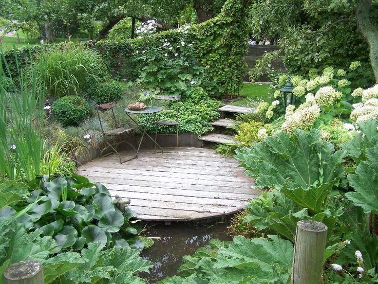 Natuurlijke tuin met houten vlonder terras bij vijver for Tuinontwerp natuurlijke tuin