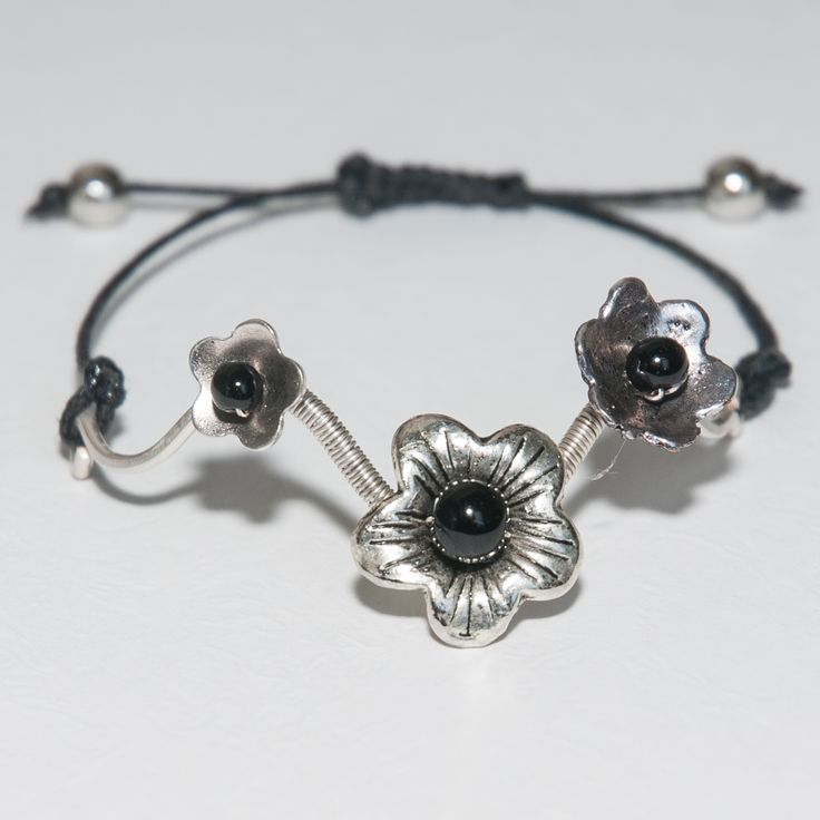Made from 10mm and 4mm silver wire with metal flower and glass beads. Adjustable clasp string.
