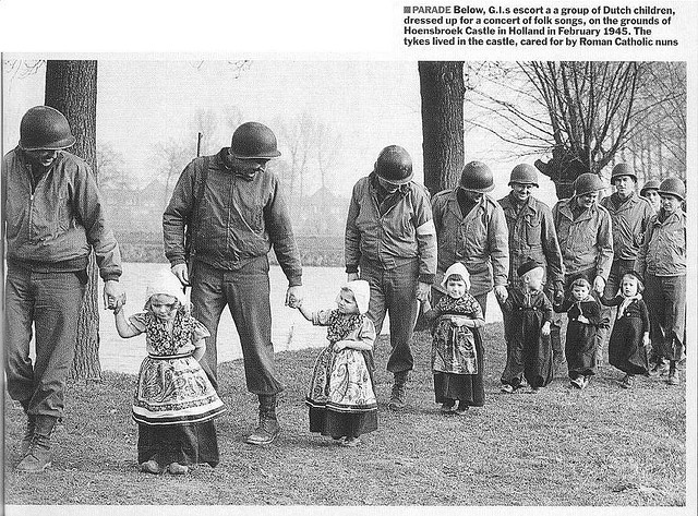 American soldiers escort a group of Dutch children after the liberation, to a folk song concert (1945)