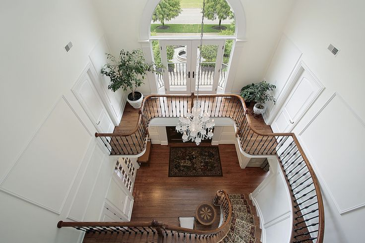 View of 2-story entrance foyer from landing with arched staircase #design #inspiration