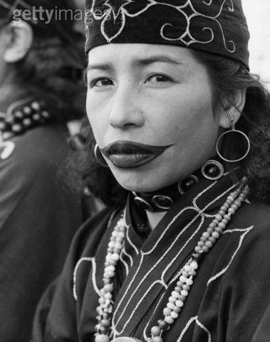 sailorx2: This is an image of an Ainu woman with traditional lip tattoo. The Ainu are the indigenous people of Japan, who some believe to have been descended from the Jomon. The lip tattoo is a purely female tradition, passed down from mother to daughter. The techniques involved include cutting the lip with special knives then taking the ash that collects in the hearth for the colouration, giving off a distinct, dark blue shade. It begins at a young age, with a semi-circle on the upper lip.