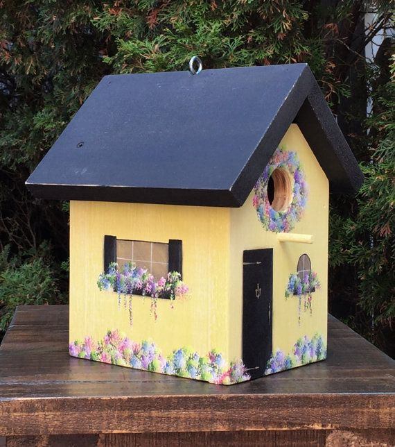 This outdoor birdhouse is painted with a matte black paint on the roof that has been sanded for a weathered finish. There is a screw eye hook in the roof for hanging and is also removable for cleaning. Pink, violet and lavender flowers adorn the house. The birdhouse has been sprayed with a matte sealer to protect the paint.  Receive a free 10 hook with this birdhouse.  Color: Black (matte) roof with wash of yellow on sides  Size: 8 wide x 10 high x 10 deep