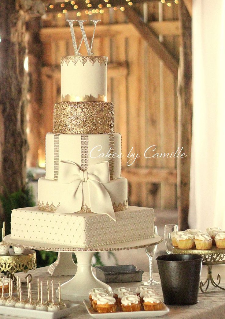 Ivory and gold wedding cake, with bow. Round and square tiers, vintage barn wedding. Cakes by Camille