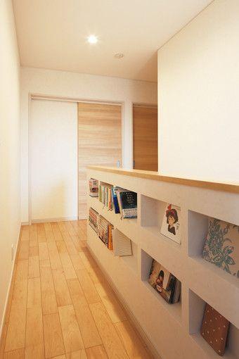 ご夫妻らしいアイディアをプラスした階段スペース。柵の一部を穿って棚をつくり、本をしまったり小物を飾ったりできるようにしている。