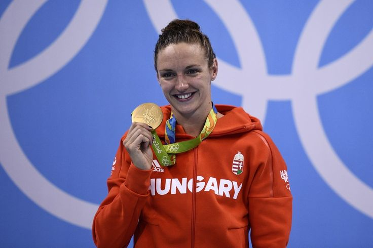 Hungary's Katinka Hosszu celebrates on the podium with her gold medal after she won the Women's 400m Individual Medley Final during the swimming event at the Rio 2016 Olympic Games at the Olympic Aquatics Stadium in Rio de Janeiro on August 6, 2016. / AFP / Martin BUREAU