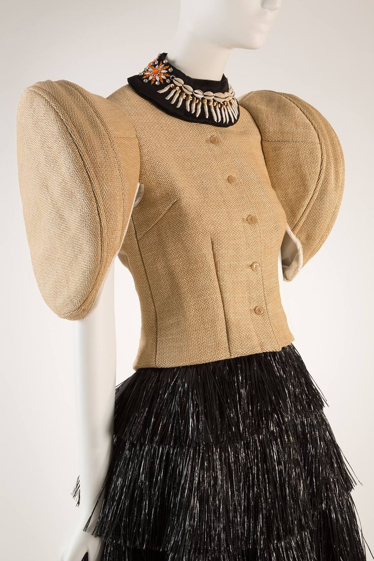 Walter Van Beirendonck raffia and cotton ensemble. Relics of the Future collection, Spring 2006. Collection of The Museum at FIT. #Antwerp #FashionCapitals  Walter Van Beirendonck, one of the celebrated designers of the Antwerp 6, was inspired by the Rapa Nui tribe of Easter Island to create this ensemble. He playfully accessorized it with a collar embellished with shells, beading, and embroidery. As head of the fashion department at the Royal Academy in Antwerp, Van Beirendonck is now…