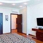 Спальня выполнена в классическом сдержанном стиле, однако использование гипсовых колонн и потолочной лепнины, придают торжественность помещению. Текстиль (шторы, покрывало для кровати, обивка кресел) в теплых пастельных тонах с легким принтом, подчеркивают интимность комнаты
