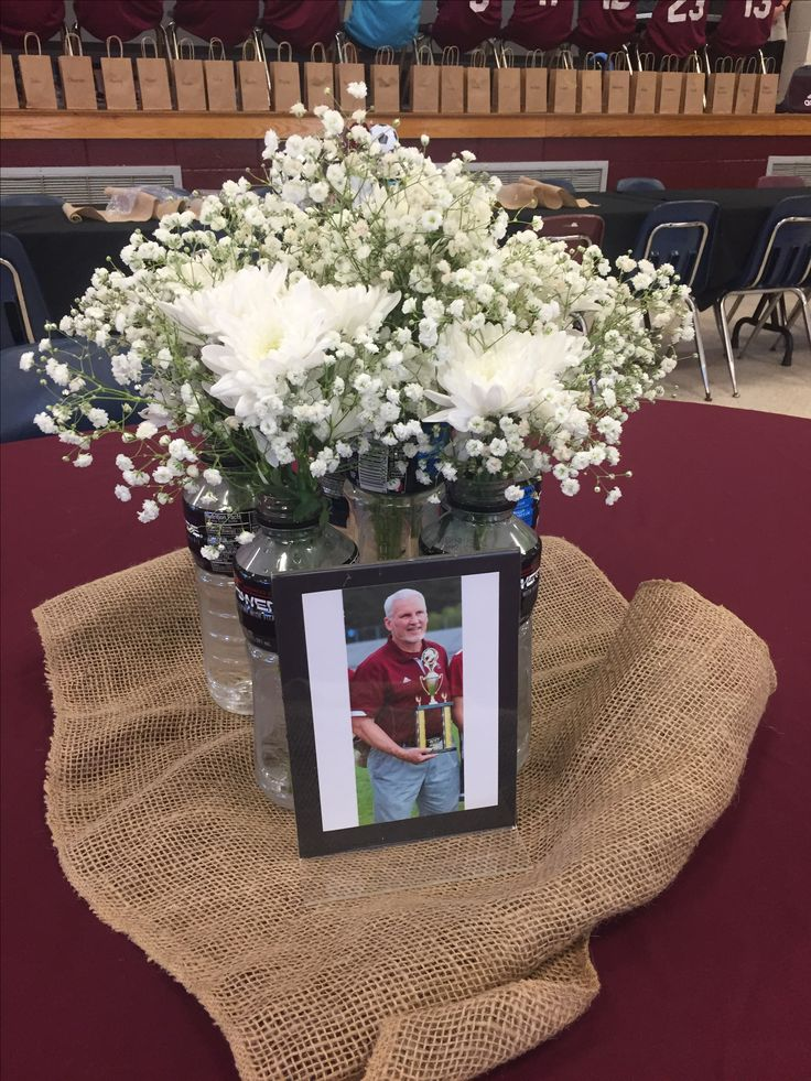 Soccer banquet centerpiece for coaches table featuring Powerade vases of flowers, burlap and coaches photo.