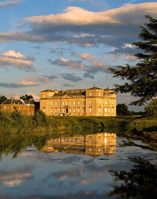 the large and golden looking Croome Court, Worcestershire, England across the water in the evening