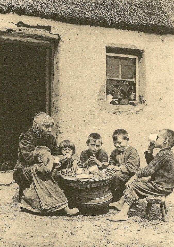 AT THE POT, CIRCA 1915-1922 photograph by A.W. Cutler and shows barefoot children eating potatoes and milk outside a cottage in Ireland with an older woman