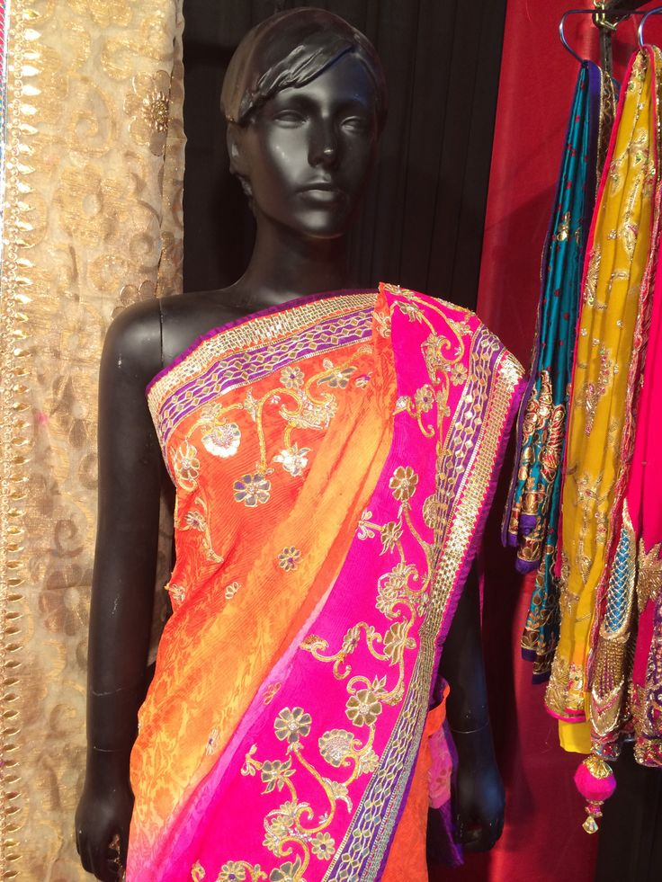Designer saree in bright orange and pink shading. Gota patti and dori handworked combined to embellish the scalloped style skirt and bale style pallu design.