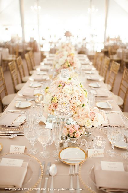 Gold beaded chargers, bread plates, crystal glasses, and pale pink tablecloth
