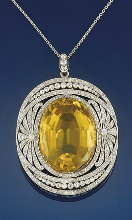 An early 20th century diamond and citrine diamond pendant   The oval citrine within a diamond openwork panel with palmette decoration and old-cut diamond collet detail, to a fine link chain, panel circa 1905