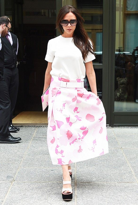 Victoria Beckham tucks a white top into a belted floral midi-skirt. Beckham finishes the look with platform sandals and a matching clutch.