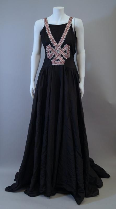 A Jeanne Lanvin black satin evening gown, 1938, the sleeveless gown with pink braid and glass bead decoration to front and back in a ribbon design.
