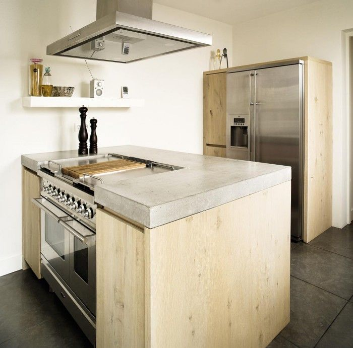 De keuken - Fornuis geïntegreerd in kookeiland. Dankzij het gebruik van ruwe materialen in combinatie met stoere RVS apparaten geven deze keuken van Fred Constant een uniek karakter. De houten kasten combineren mooi met het RVS van de koelkast, afzuigkap en het fornuis. Het robuuste fornuis is zeer fraai ingebouwd. Het werkblad van beton maakt het robuuste karakter van deze keuken compleet.
