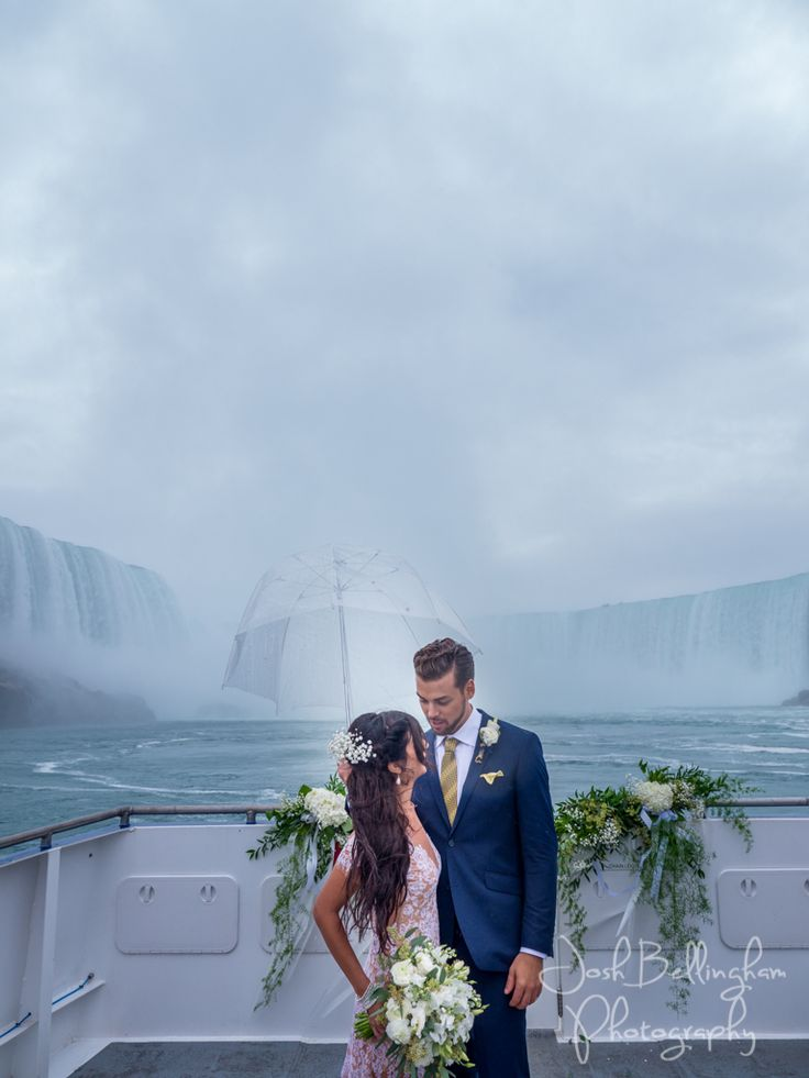 Super Romantic photo of bride and groom right under Niagara Falls. Aboard the Guardian, Hornblower Niagara Cruises Wedding boat. Gorgeous bride with lace dress and groom with stylish blue suit. Elopements under Niagara Falls. #JoshBellinghamPhotography