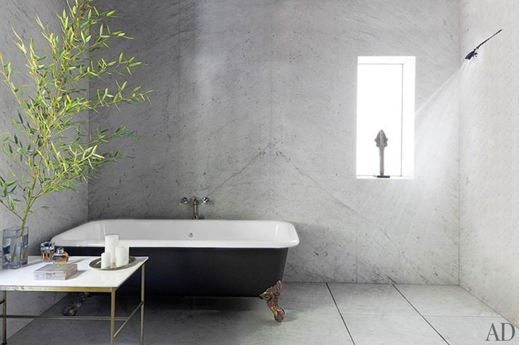 Adam Levine's minimalist bathroom is home to an antique claw-foot tub and a Paul McCobb table