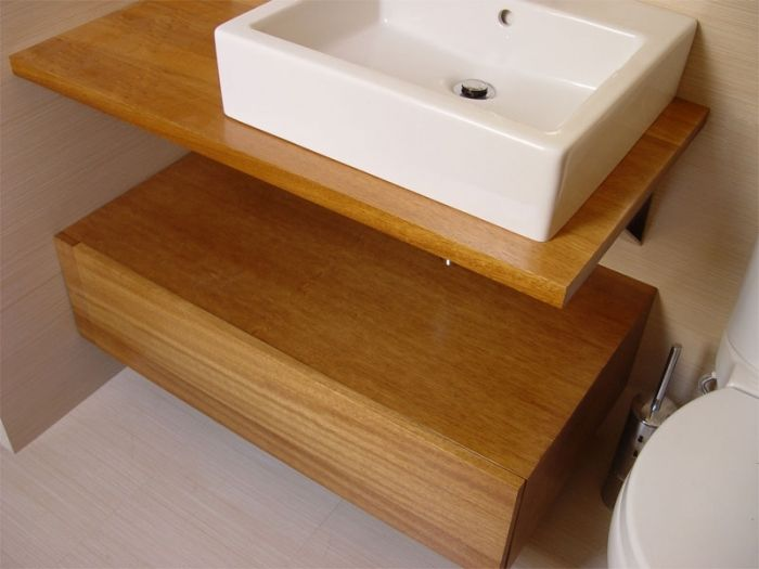 Diseño y fabricación de encimera de baño a medida y mueble de lavabo realizado con madera de iroko alistonado, acabado barnizado