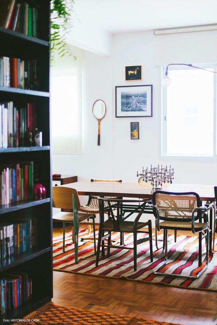 Detalhe da sala de jantar com tapete colorido listrado e cadeiras de design descombinadas.