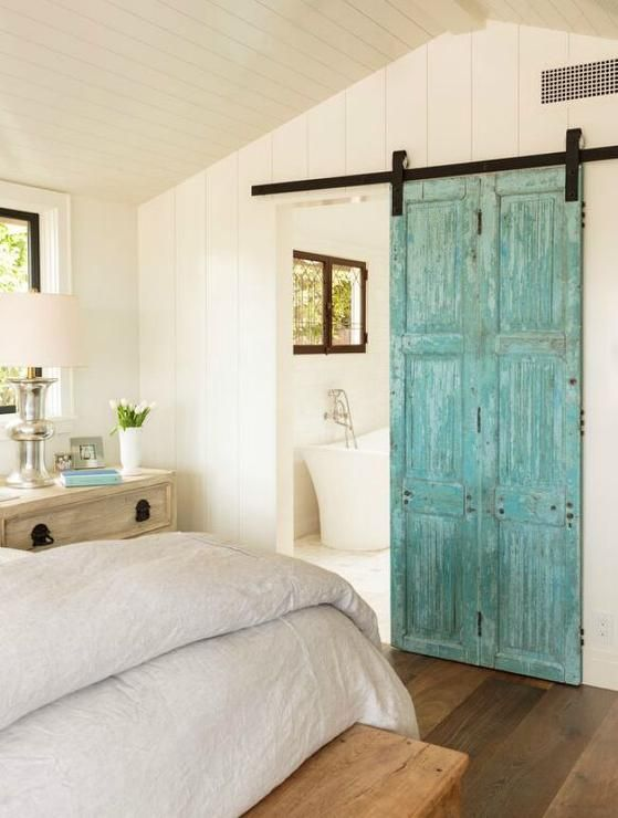 A gorgeous cottage bedroom is filled with a bed dressed in a gray linen duvet next to a distressed ...