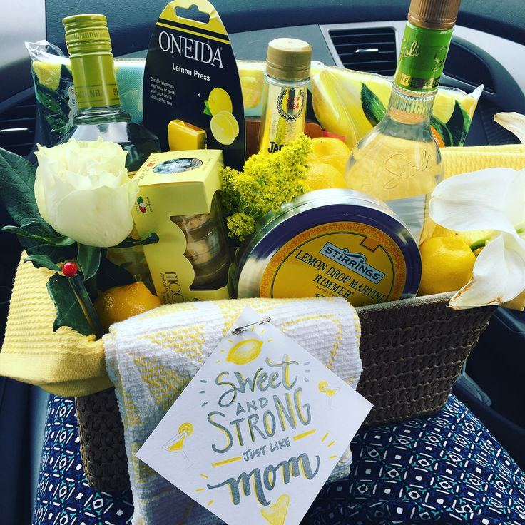 Lemon drop martini kit gift basket with citrus vodka, triple sec, macarons, lemons, sugared rim met, lemon-yellow towels, mini cutting board, tablecloth and lemon press. Pin on a sweet message and you're golden! #lemon #lemondrop #giftbasket #liquor #drinkmix #giftformom