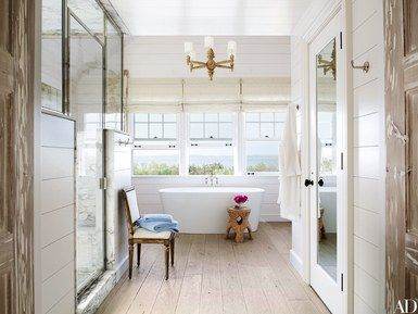 The master bath of a Southampton, New York, retreat by interior designer David Netto and architect David Hottenroth has a Wetstyle tub with Waterworks fittings, a Paul Marra spool chandelier, Roman shades of a Larsen linen blend, and a chair from Cove Landing | archdigest.com