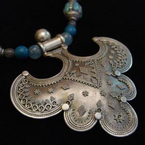 collier dans les tons bleu, entre turquoise sombre et bleu canard. Il est composé de perles en résine, en céramique, en bois, en Argent et en pierres semi-précieuses (Turquoise, Quartz fumé bleuté et Agates teintées). Le pendentif Argent très original est originaire d'Inde. Certaines perles en Argent sont originaires du Triangle d'or (Nord Thaïlande, Laos, Birmanie), d'autres sont issue du Tibet.