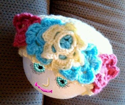 Head is surrounded with flowers on this little hat.  Rose/salmon colors and blue/yellow flowers.