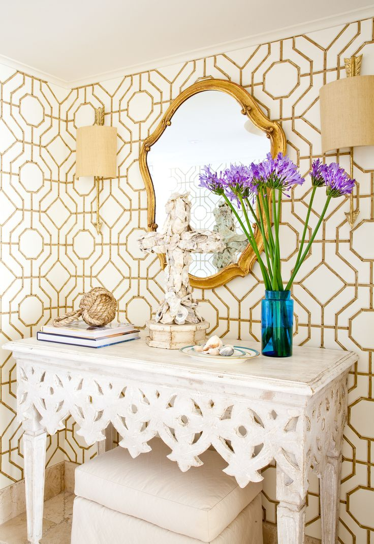 Don't shy away from mixing and matching bold patterns.  This metallic gold and white wallpaper go beautiful with the detailing in this stunning sideboard.