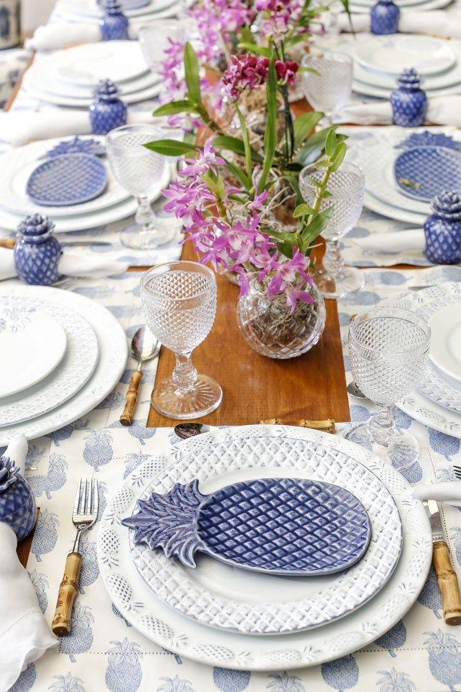 Mesa para almoço montada no jardim com estilo piquenique e louças com desenhos de abacaxi da loja Theodora Home em tons de azul e branco.