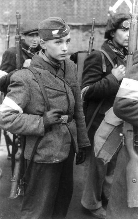 Polish insurgents of the Polish Home Army, wearing the flag of Poland as armbands and carrying their rifles to ready themselves for combat against German occupying forces during the Warsaw uprising, 1944