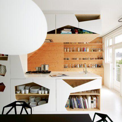 Une cuisine ouverte avec un meuble cloison qui la sépare du salon Des petits trous, encore des petits trous, pour ce meuble cloison qui permet de ranger avec style : livres et vaisselles, dont les bols et les tasses de chez IKEA, trouvent leur place. Au fond, la cuisine, tout de bois vêtue, est ultra fonctionnelle. Une étagère accueille des dizaines de pots alignés de chez IKEA.