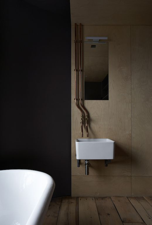 Ironmongers' Quarters - Flat 1   Jonathan Tuckey Design, Hackney Road, East London - The bathroom finished with birch plywood paneling, butler sink, copper piping and taps.