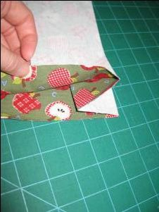fold the bottom in and it will be caught in the side seam, making a boxed corner