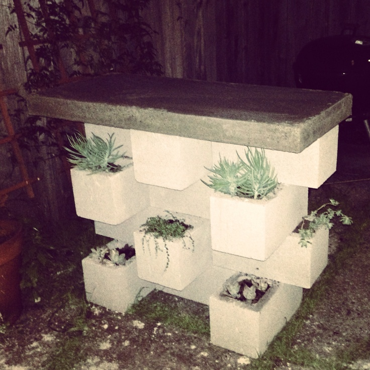 Outdoor bar with concrete cinderblocks and planters a la apartment therapy. Wooden top replaced with concrete slab to accommodate BBQ paraphernalia. Succulents planted in cinderblocks.