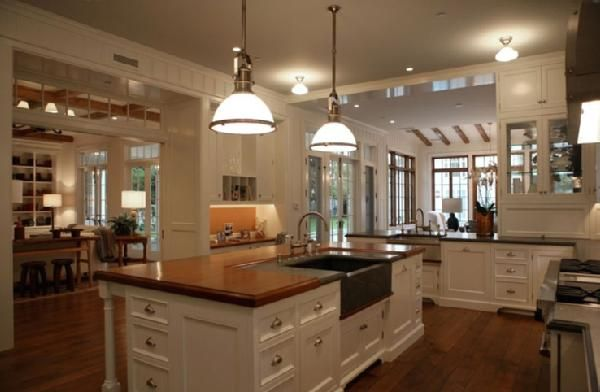 Love this kitchen....butcher block counters with ivory cabinets.  Also love the lights and kitchen sink in the island!