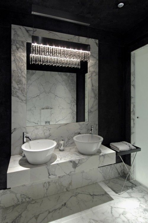 designer michael habachy uses black venetian plaster walls to contrast dramatically with the bathrooms white marble vanity area